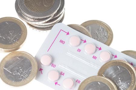 birth control: las p�ldoras anticonceptivas con las monedas de euro sobre un fondo blanco Foto de archivo