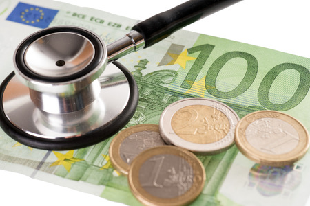 Stethoscope with 100 euro banknote and euro coins photo