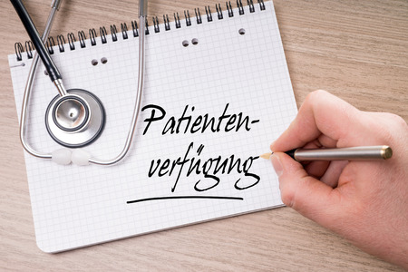 bereavement: Writing pad and hand with pen writing the german words advance directive