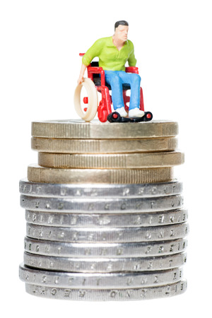 wheelchair user on a stack of euro coins isolated over a white background photo