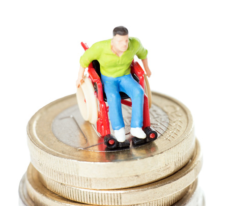 Wheelchair user on a stack of euro coins over a white background