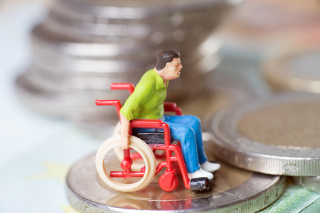 Wheelchair user with euro coins and euro banknote photo