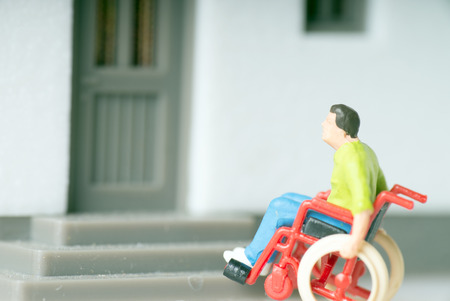 Wheelchair user in front of a house photo