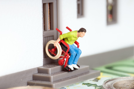 Wheelchair user on an exterior staircase and euro money photo