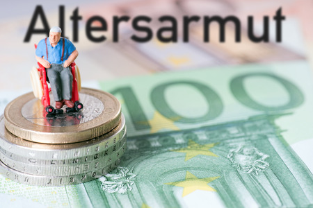old man in a wheelchair with money and the german word pensioner poverty photo