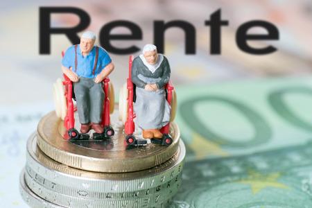 Stary człowiek na wózku inwalidzkim z pieniędzmi i niemieckiego słowa emerytura