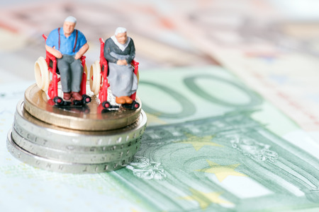 Old couple in a wheelchair with euro money Stock Photo