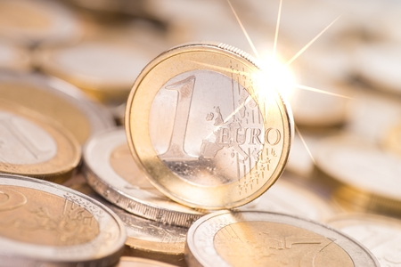 household money: sparkling Euro coin with coin stack
