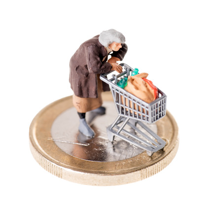 Old woman with shopping cart on a coin photo
