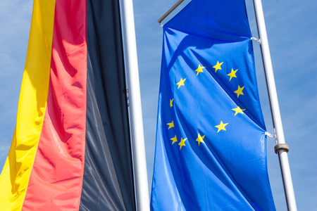 Germany flag with flag of Europe and blue sky photo