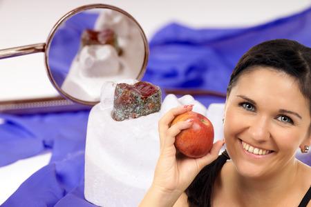molares: mujer joven con manzana delante de una dentadura con espejo dental Foto de archivo