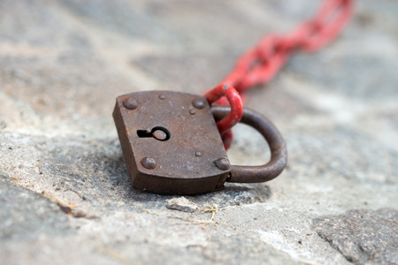 connectedness: old padlock on a red chain