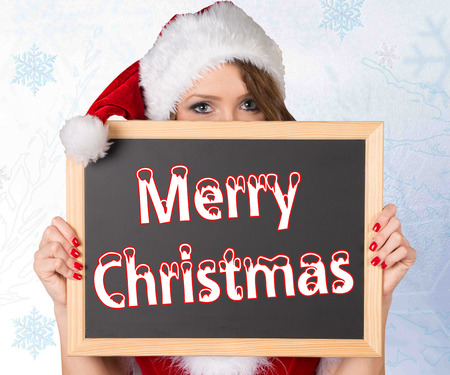 Woman in christmas costume and chalkboard with the words merry christmas