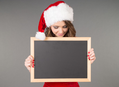 Woman in christmas costume and empty chalkboard photo