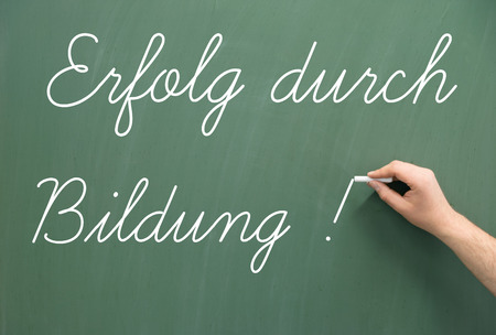 retraining: Chalkboard with the german words Success through Education