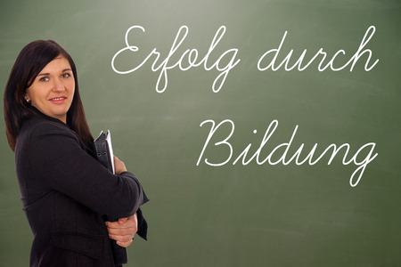 retraining: young woman in front of a blackboard with the german words Success through Education