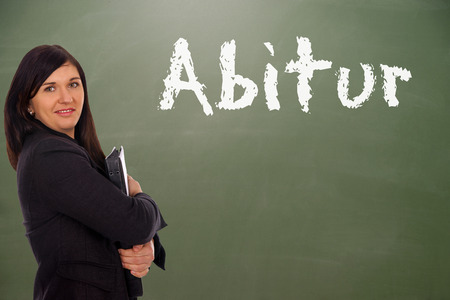 abi: Student in front of a blackboard with the german word Abitur