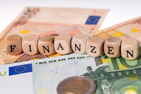 deposits: Banknotes and wood cubes with the german word finance