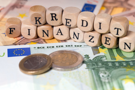 editions: Euro money and wooden cubes with the german words Finance and Credit Stock Photo