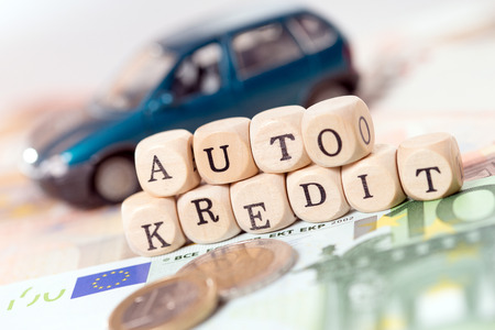 car loan: Money and wood cubes with the german words car loan