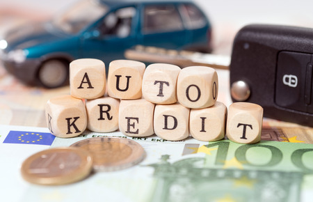 auto leasing: money and wood cubes with the german words car loan