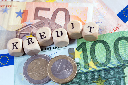 Euro Money and wood dice with the german word credit photo
