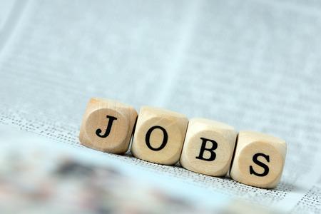 puesto de trabajo: Dados de madera con la palabra empleo en un peri�dico