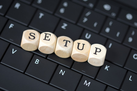 Keyboard and wood dice with the word Setup Stock Photo