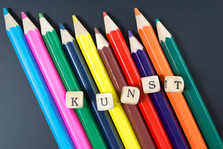 colored pencils: Colored pencils and wood dice with the german word art