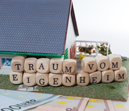 home ownership: Euro Banknotes with Wooden cubes and the german words dream of home ownership Stock Photo
