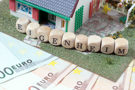 home ownership: House and wooden dice with the german word Home Ownership
