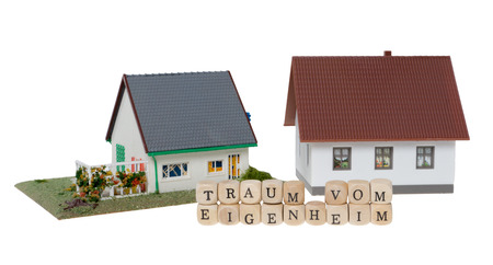 home ownership: Wooden cubes and the german words dream of home ownership isolated over a white background Stock Photo