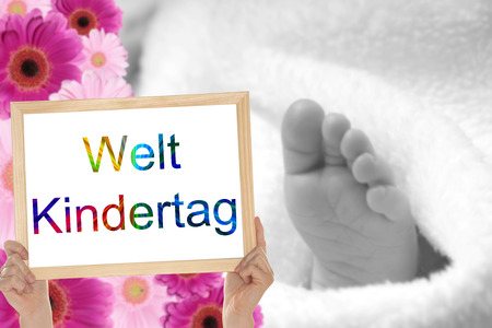 commanded: small feet and shield with the german words World Children Day Stock Photo