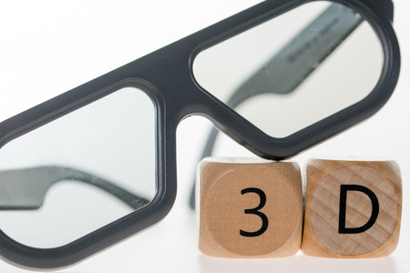 three dimensions: 3D glasses and wooden cube with 3D Stock Photo