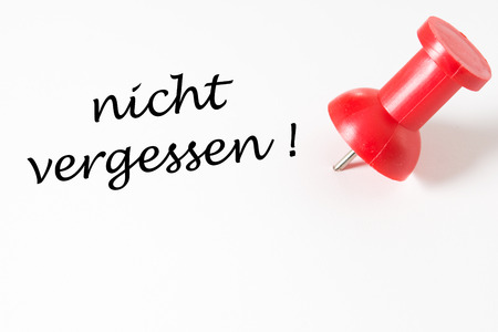 pin needle: red pin needle and the german words do not forget Stock Photo