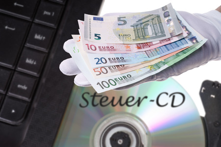 treaties: Computer with Tax evaders CD and Euro money Stock Photo