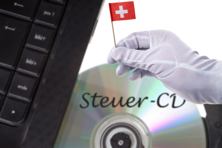 Computer with Tax evaders CD and Swiss flag photo