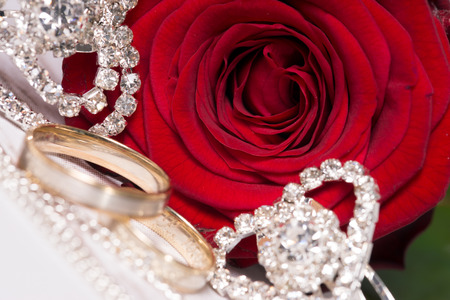 diamond rings: red rose and small diamond encrusted hearts with wedding rings