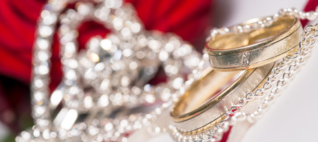 red rose and small diamond encrusted hearts with wedding rings photo