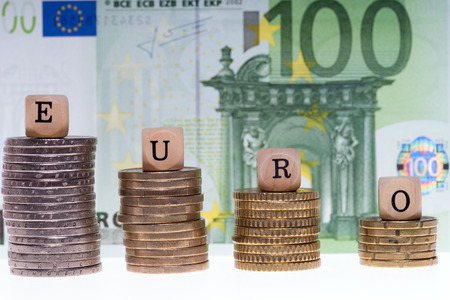 household money: Money stack and wood dice with the word Euro Stock Photo
