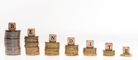 remuneraciones: Pila de monedas y dados de madera con la palabra alemana retorno de la