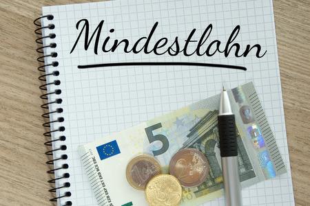 minimum wage: Pista de escritura con el dinero y el salario m�nimo alem�n palabra Foto de archivo