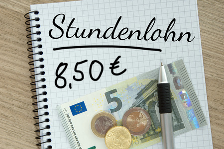 monthly salary: Writing pad with money and the german words hourly wage