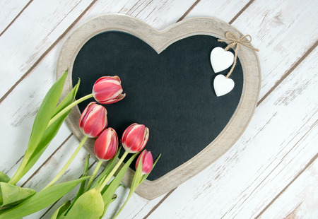 cordial: Wooden panel in heart shape with tulips Stock Photo