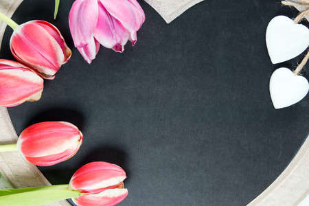 Wooden panel in heart shape with tulips photo