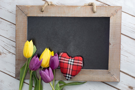 empty blackboard with wooden frame with tulips and little heart photo