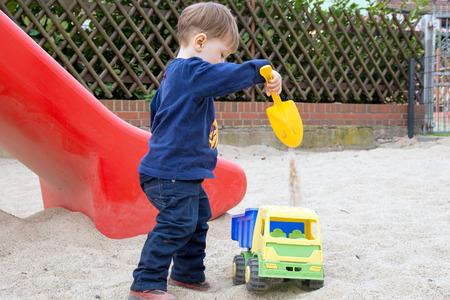 sandbox: little boy in a sandbox with toys Stock Photo