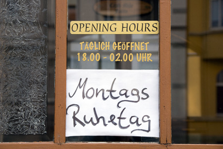 closing: Sign with opening times and the German words Monday Closing Day