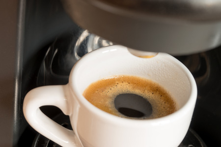 a cup of espresso is brewed