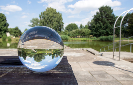 glass sphere: Glass sphere picture in nature with blue sky Stock Photo